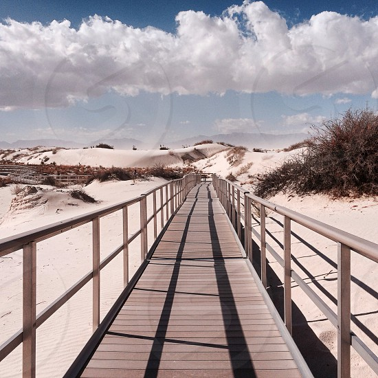 view of wooden walkway on white sand under cloudy sky photo