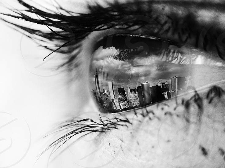 grayscale photography of reflection of high rise buildings on persons eye photo