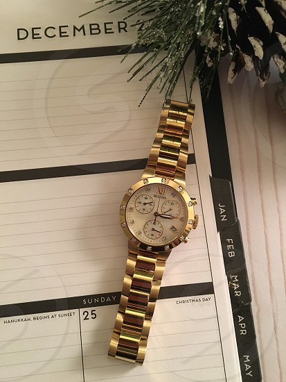 gold link bracelet chronograph watch at 3:15 over organizer book photo
