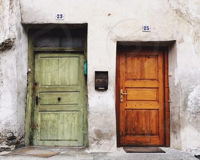 Green and brown doors on rustic Northern Italian buildings photo