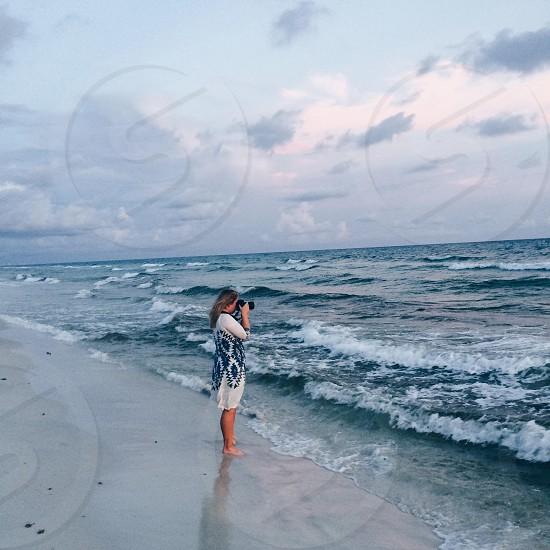 woman taking photo at seashore photo