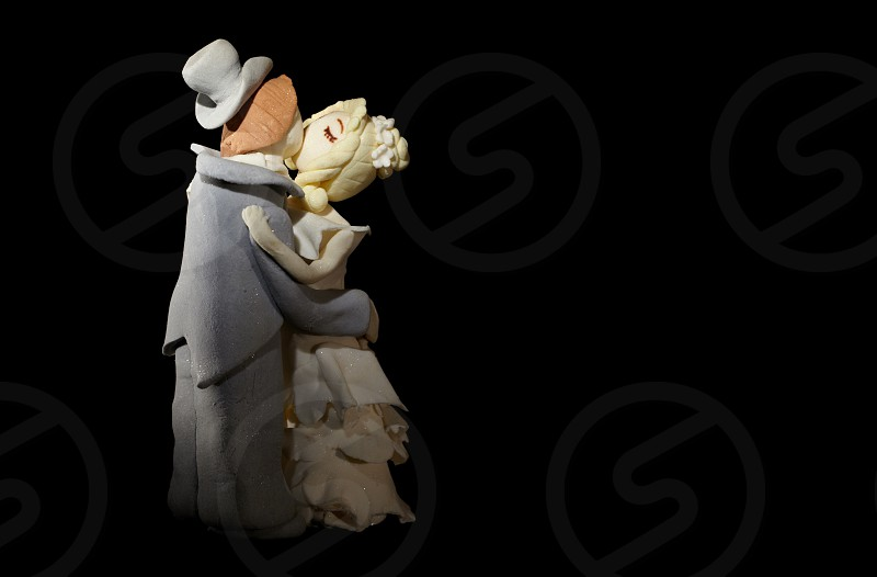 Wedding cake figurines are kissing on black. photo