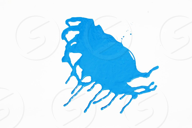 Blue liquid spreading out on a white background photo