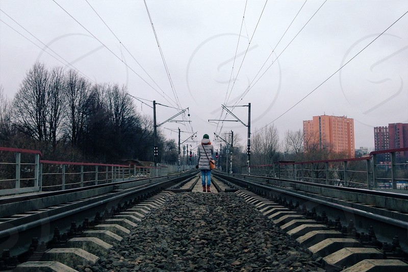 woman in white and gray striped shirt and blue denim jeans standing on train tracks during daytime photo