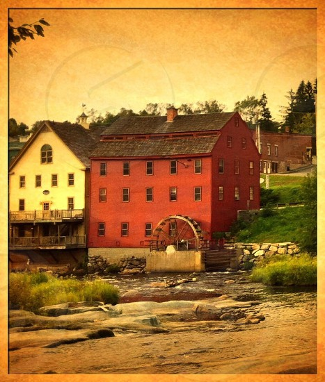 red 4-storey house with water mill outside photo