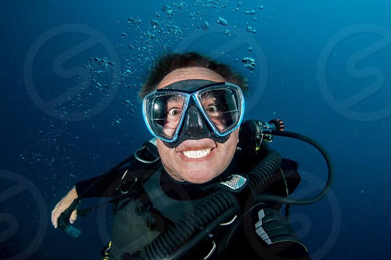Happy scuba diver smiling underwater photo