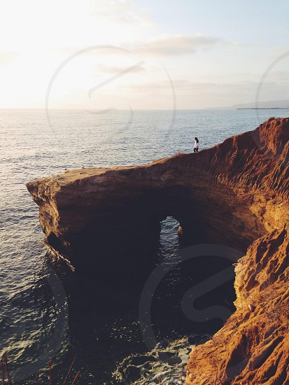 person standing on cliff over ocean photo