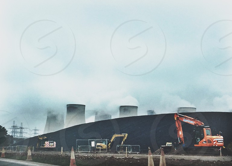 3 excavator at the side of a nuclear power plant photo