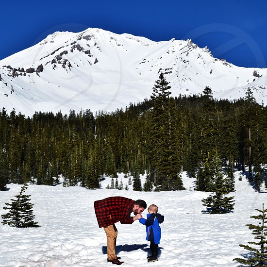 Mount Shasta mountain snow discovery forest trees pines father son warming hands blue sky photo