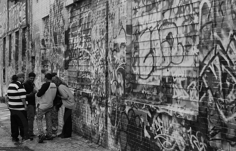 people standing beside a grey concrete wall with graffiti photo