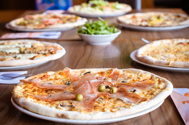 Multiple pizzas served on a group table in a restaurant. photo
