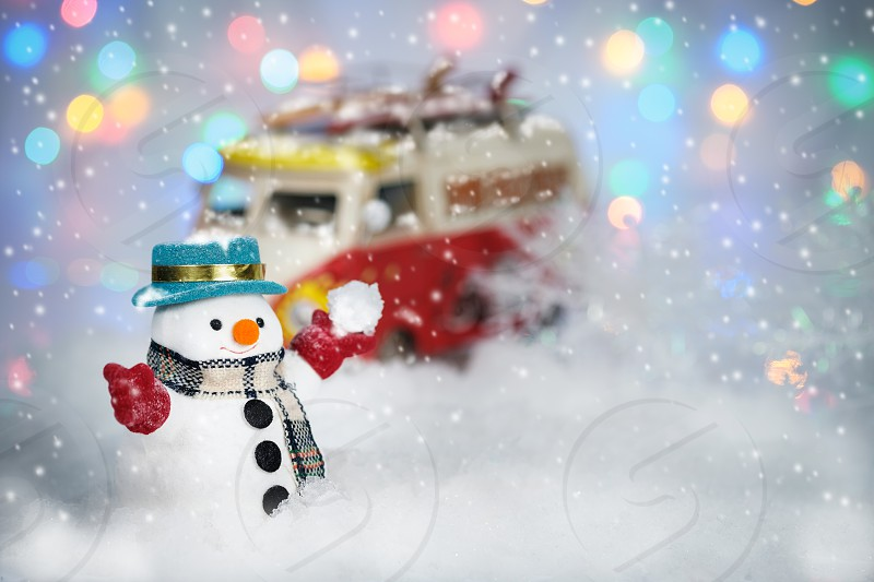 A snowman playing snow near mini car. photo
