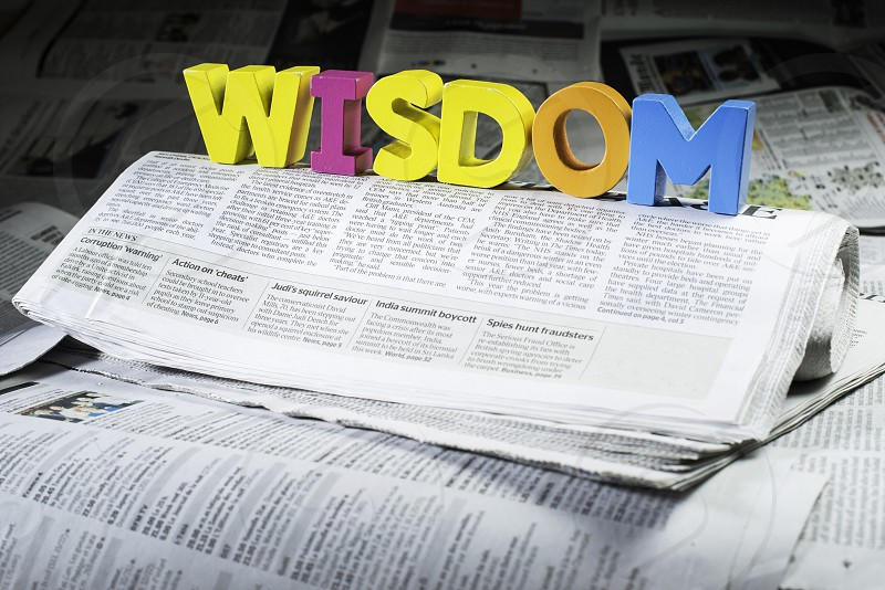 Word wisdom on newspaper.Wooden letters photo
