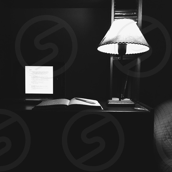 pen on opened book beside black and white table lamp photo
