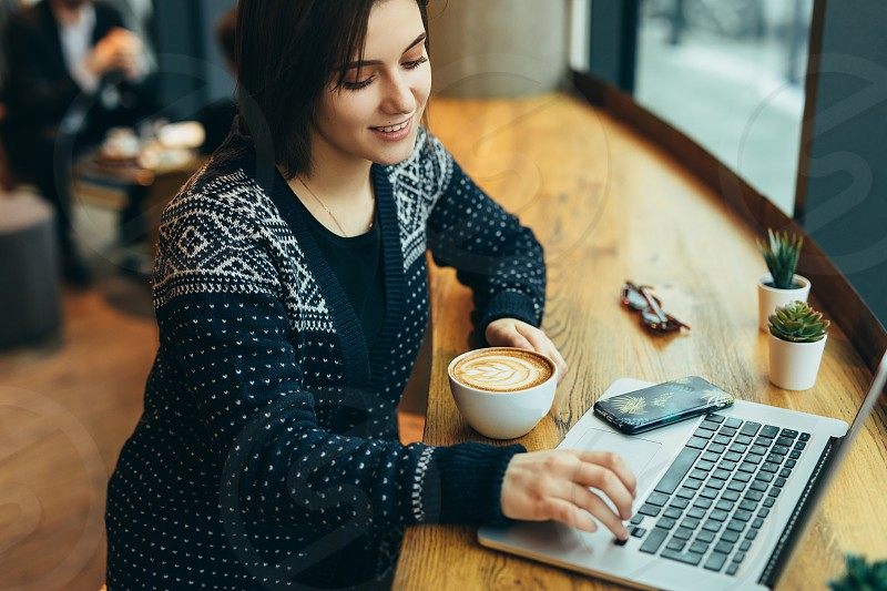 Woman Look Around And Smile While Work In Cafe On Her Laptop. Portrait Of Stylish Smiling Woman In Winter Clothes Work At Laptop. Female Bussiness Style With Sun. - Image photo