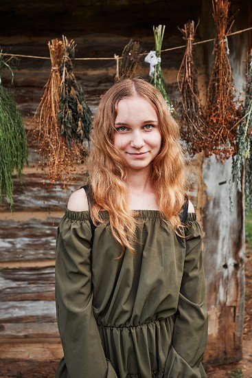 Portrait of young woman  standing in front of old cottage and hung some withered species of herbs. Girl is wearing green dress looking at camera photo
