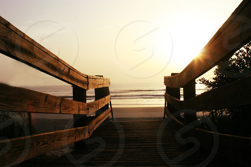 """Brillinace"" A sun sets on a beach walkway. photo"
