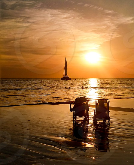 Dramatic Sunset at the beach with a couple shadow enjoying it and a boat photo