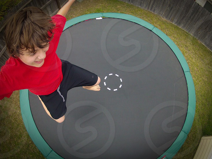 boy in red shirt jumping on trampoline  photo