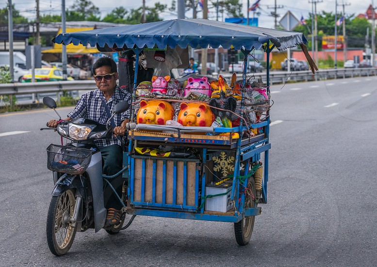 A street vendor on way to market with his piggybanks. Taken in Thailand. photo