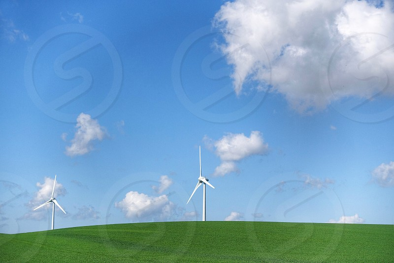 2 white windmills on green grass field under blue sky and white clouds photo