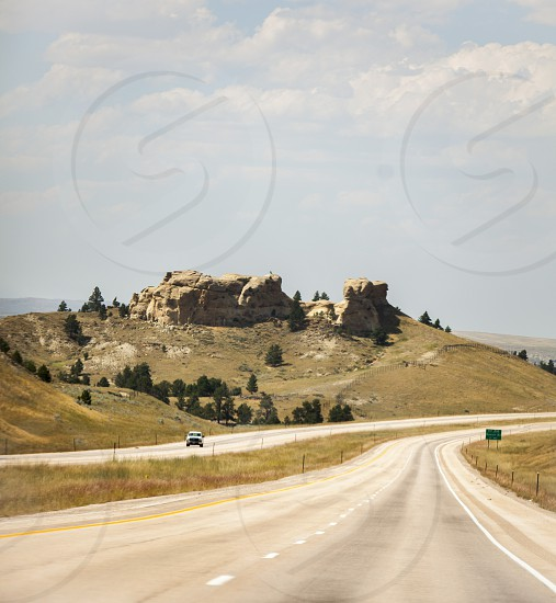 Driving through Wyoming with a view of a butte photo