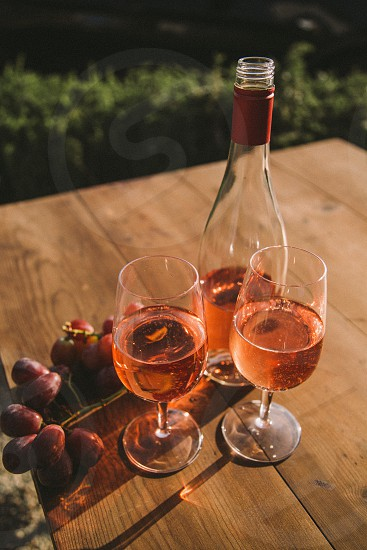 two wine glasses filled with rose wine on a table next to the bottle and purple table grapes surrounded by green grass under the sun photo