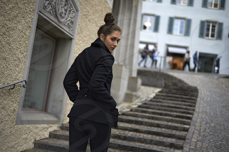 Beautiful young caucasian woman walking up the stairs in the old town of the city centre of Zurich and looking back over her shoulder photo