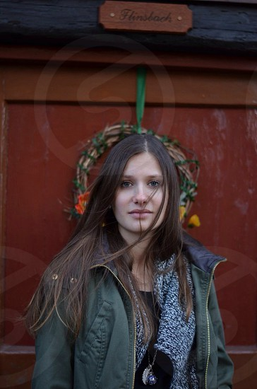 woman with long brown hair in olive khaki coat and black marled boucle sweater near wreath photo