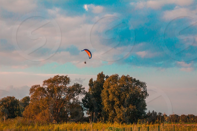 Motorized paraglider flying in rural area during sunset photo
