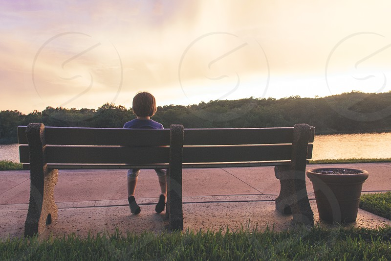 child sitting on bench near body of water photo