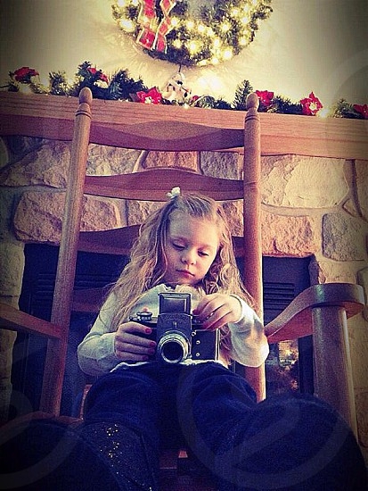 Little girl playing with camera .. Christmas setting  photo