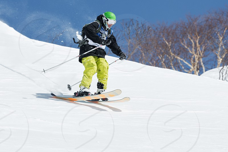 "KAMCHATKA RUSSIA - MARCH 9 2014: Skier rides steep mountains. Competitions freeride snowboarders and skiers ""Kamchatka Freeride Open Cup"". Russia Far East Kamchatka Peninsula. photo"