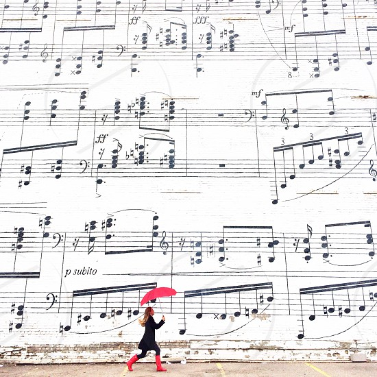 woman walking with red umbrella near music sheet wall photo