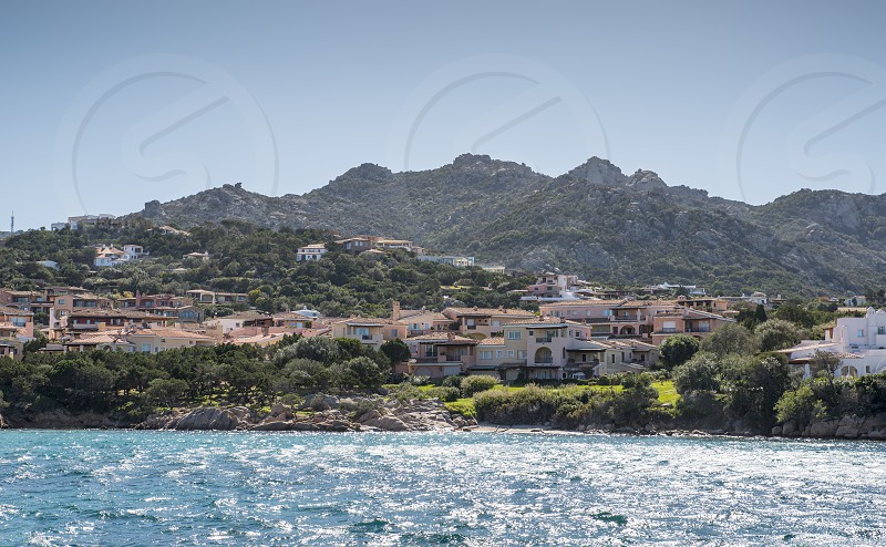 skyline of ht exclusive village of porto servo on sradinia island italy with the mountains as background and the blue water in the sea as foreground. photo