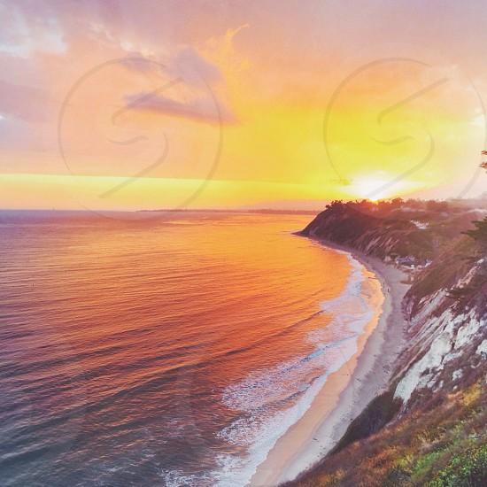 sunset over rocky shoreline photo