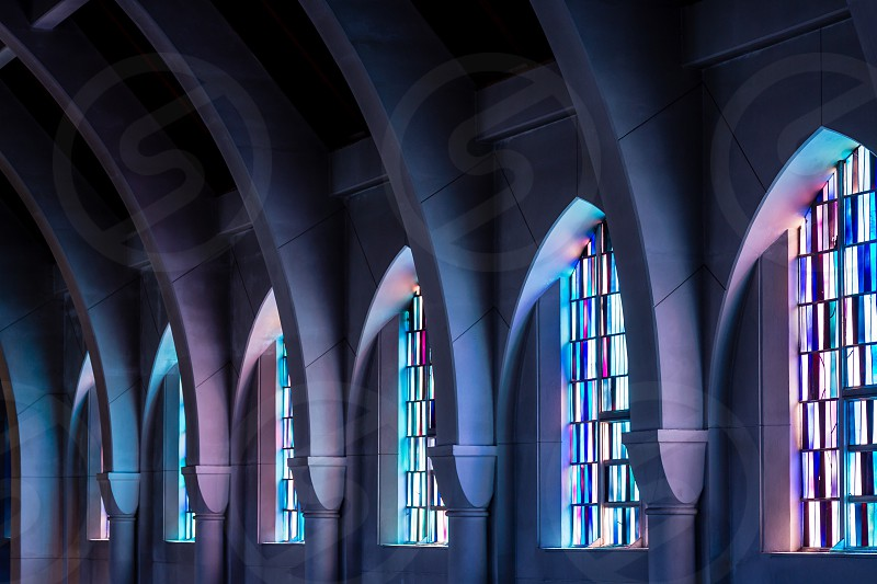 Arched columns in monastery chapel with stained glass windows photo