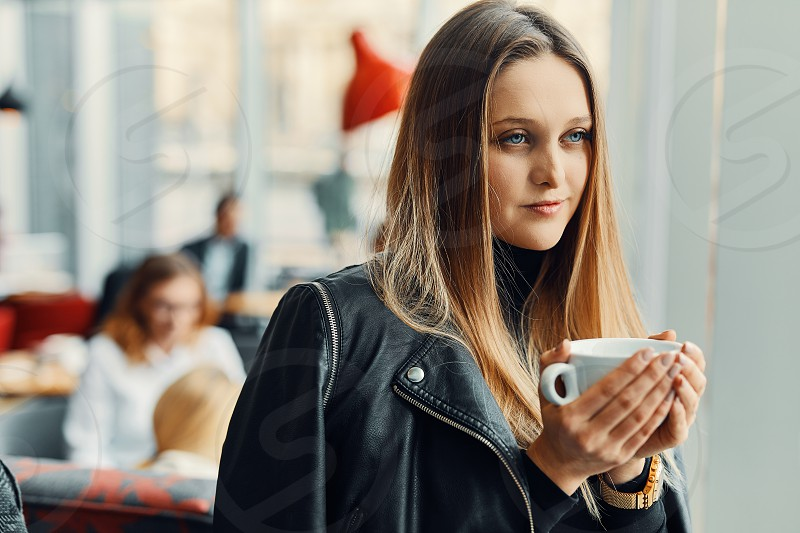Pretty girl stand near the window with cup of coffee and smile photo