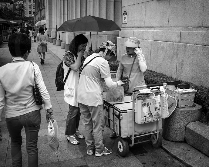 Old women sell yogurt from a cart in Seoul. photo