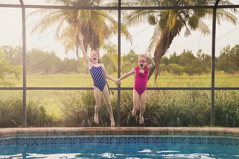 Two little girls jumping in the pool on a warm summer night photo