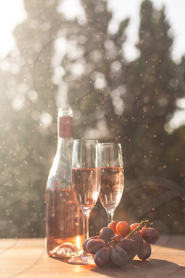 two champagne flutes filled with rose wine next to the bottle and purple table grapes under the sun photo