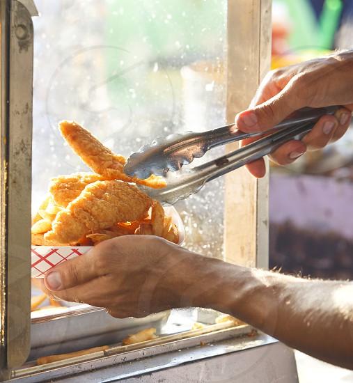 Hands serving chicken tenders photo