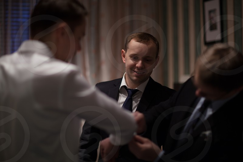 Two friends helping a groom to get ready for wedding ceremony by fixing cuff links photo