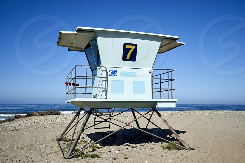 Beach lifeguard tower on the California coastline against blue skies photo