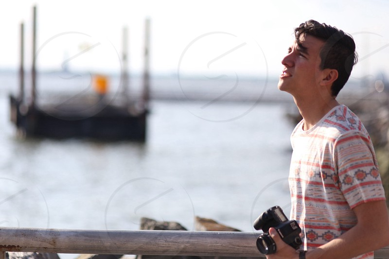 man wearing a striped shirt standing by a rail overlooking water and a floating dock photo