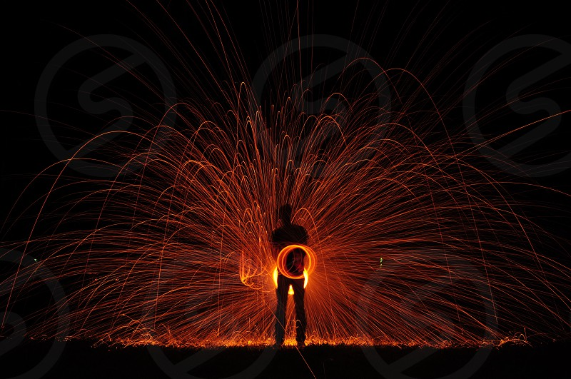 light motion photo of silhouette of person using orange sparkler photo