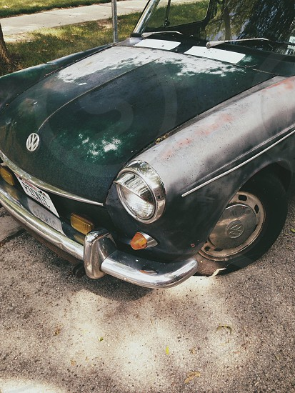 vintage dark green volkswagen car with chrome accents parked on curb near grass under tree photo