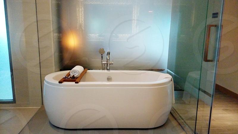 white towel on white ceramic bathtub photo