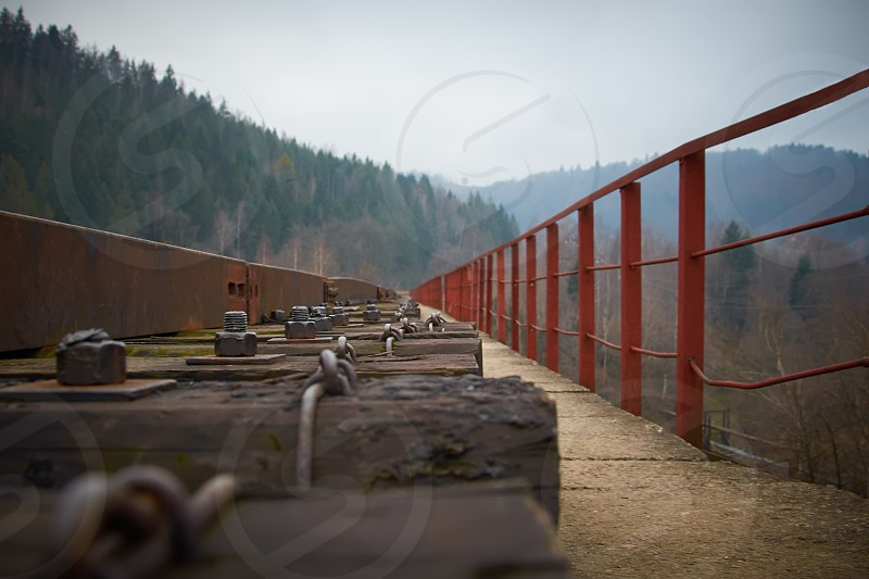 green old metal business outdoors travel nature road transport move tree mountain track sleepers forest culture motion traditional iron rust rusty hill cargo bridge nut bolt railing railroad obsolete fastening along  photo