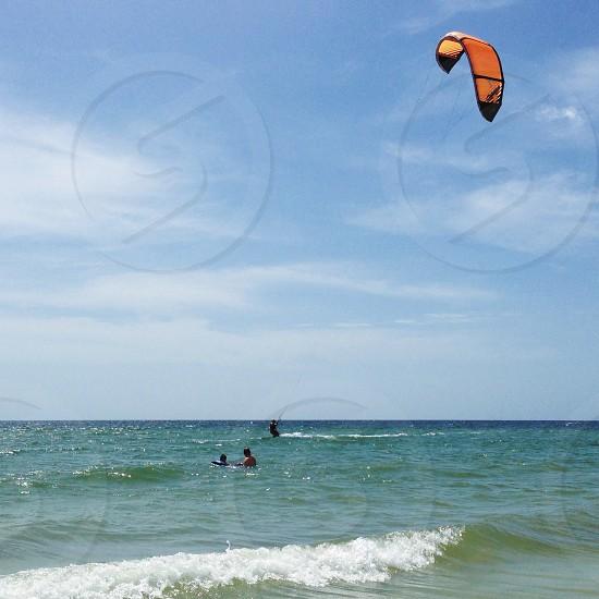 3 man swimming on beach photo